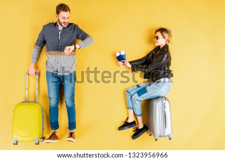 Woman sitting on valise with tickets while man looking at watch on yellow background