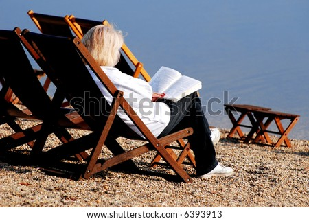 Woman sitting on wooden bench and read the book near lake