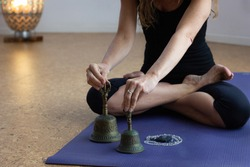 Woman sitting on yoga mat in lotus pose holding metal bells by mala beads necklace. Anonymous yogi on padmasana with accessories for meditation ritual in studio. Relax, zen concepts