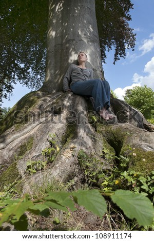 woman sitting under a tree - stock photo