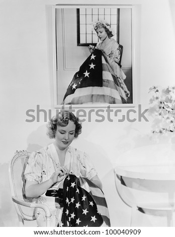 Woman sitting under the portrait of Betsy Ross sewing the American flag