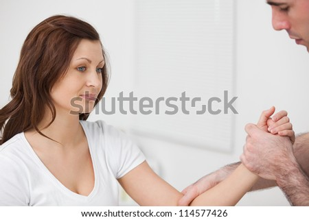 Woman sitting while a man examine her arm in a room