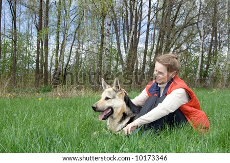 Woman sitting with alsatian dog on grass at nature