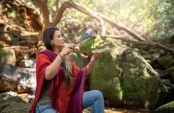 Woman sitting with her eyes closed in a forest and performing a cleansing ceremony with incense and a smudging wand