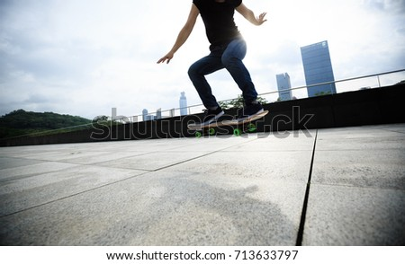Woman skateboarder skateboarding at sunrise city #713633797