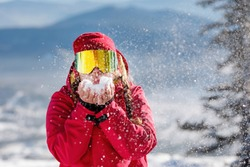 Woman skier blows snow from her palms. Blue mountain slopes. Red hooded jacket, yellow ski goggles. Healthy lifestyle. Sports concept. Selective focus.