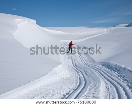 Woman skiing alone in a groomed curved double ski track with a characteristic wind swept snow formation on her left in the norwegian mountains at easter