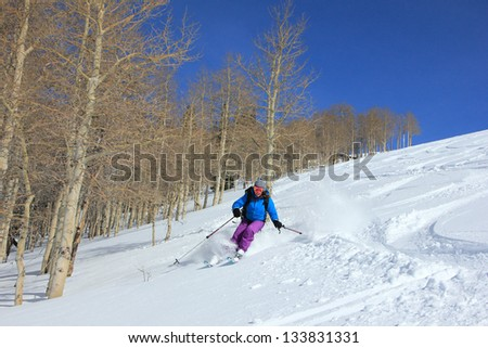 Woman skiing beside aspen trees in the Utah mountains, USA.