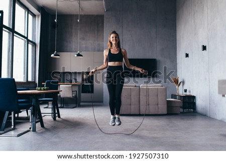 Woman skipping with jump rope at home.