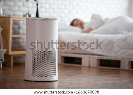 woman sleep with Air purifier in cozy white bed room for filter and cleaning removing dust PM2.5 HEPA in home,for fresh air and healthy life,Air Pollution Concept