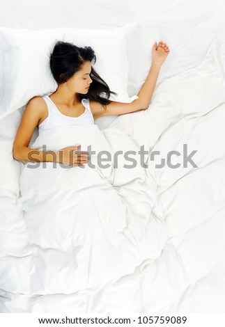 Woman sleeping and resting alone in her bed, dreaming. view from above