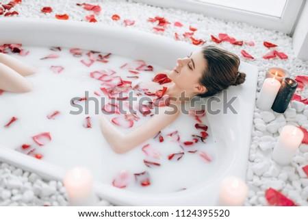 Woman sleeps in the bath with foam, rose petals