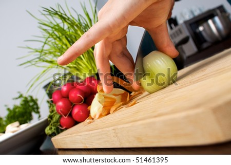 Woman slices an onion on a cutting board