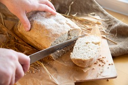 Woman slices fresh bread. hands with a knife. Freshly baked rye bread on a wooden board. Burlap, craft paper and straw on the background. Organic bread baked at home from wheat flour. Sliced bread.