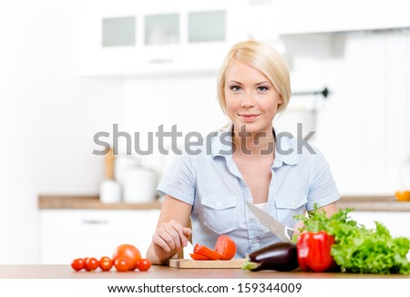 Woman slices groceries for salad sitting at the kitchen table