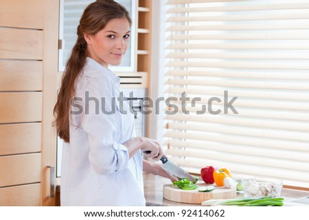 Woman slicing a pepper in her kitchen