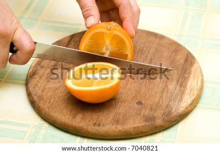 woman slicing fruit on kitchen table making fruit salad