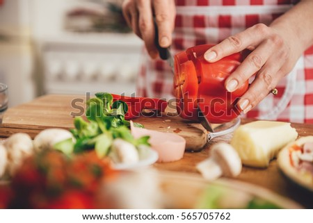 Woman slicing paprika on cutting board at the kitchen #565705762