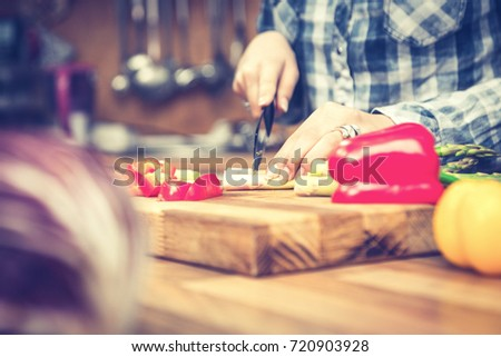 Woman slicing vegetables in the kitchen. Close up of chef cooking healthy food. #720903928