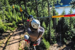 Woman sliding on a zip line in an adventure park