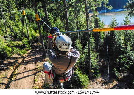 Photo of  Woman sliding on a zip line in an adventure park