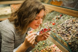 Woman smell aromatic herbal tea leaves from all the world on grand Bazaar in Istanbul, Turkey