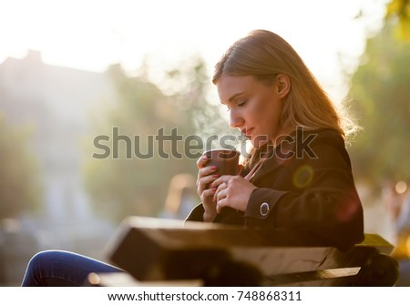 Woman smelling and drinking hot coffee during autumn sunset at the street