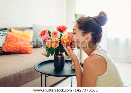 Woman smelling fresh roses in vase on table. Housewife taking care of coziness in apartment. Interior and decor