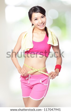 Woman smile measuring shape of waist with after sport for Healthy lifestyles concept with nature green background, model is a asian beauty
