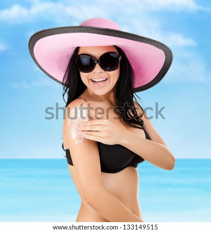 woman smile moisturizing applying sun cream on her tanned arm hands, summer vacation beach, sun tanned body, girl wear pink hat, sunglasses, over sea blue sky, concept holiday travel