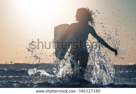 Woman smiles and runs into the sea with lots of splashes