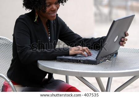Woman smiles as she looks at the computer.