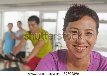 Woman smiling and exercising on the exercise bike
