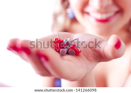 Woman smiling and holding straight pins - stock photo