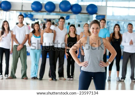 woman smiling and standing in front of a group of gym people