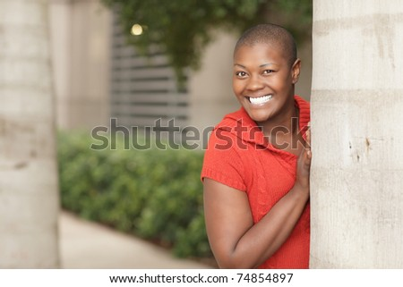 Woman smiling from behind a tree