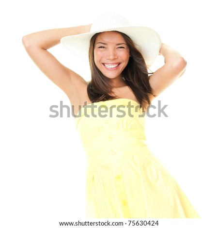 Woman smiling in summer dress playful and cheerful. Isolated on white background. Beautiful cheerful young mixed race ethnic female model in yellow dress and summer hat.