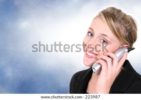 Woman smiling, talking on cordless home phone.