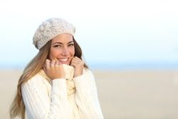 Woman smiling warmly clothed in a cold winter on the beach