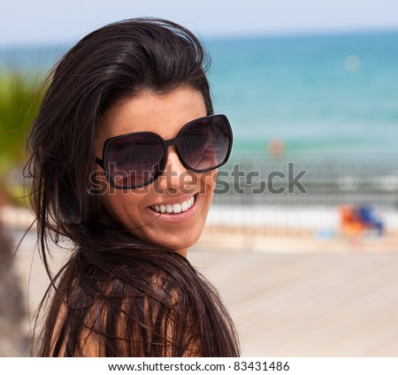 woman smiling wearing sunglasses in the beach