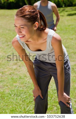Woman smiling while bending over to recover as a man is walking close behind her