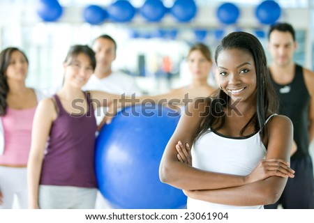 woman smiling with a group of gym people on the background