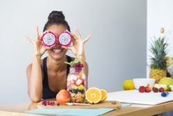 Woman smiling with a tropical fruit salad, being playful covering her eyes with dragon fruit