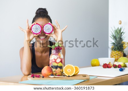 Woman smiling with a tropical fruit salad, being playful covering her eyes with dragon fruit #360191873