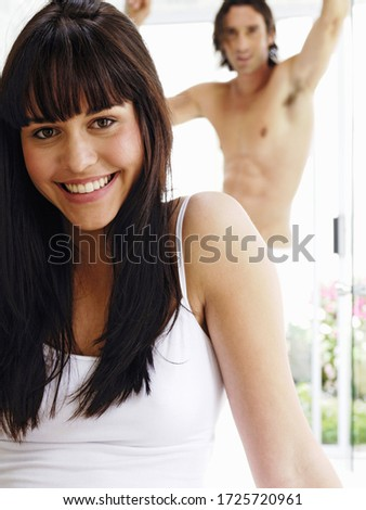 Woman smiling with boyfriend in background