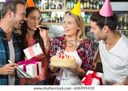 Woman smiling with cake in hands with friends cheering