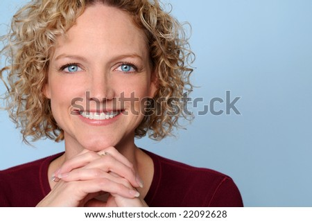 Woman smiling with hands clasped over a light blue background
