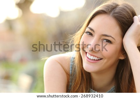 Woman smiling with perfect smile and white teeth in a park and looking at camera #268932410