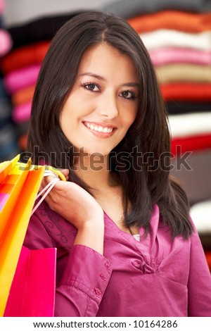 woman smiling with shopping bags in a shopping centre