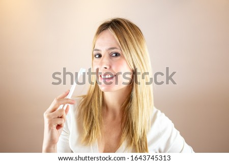 Woman smiling with toothbrush and looks into the camera